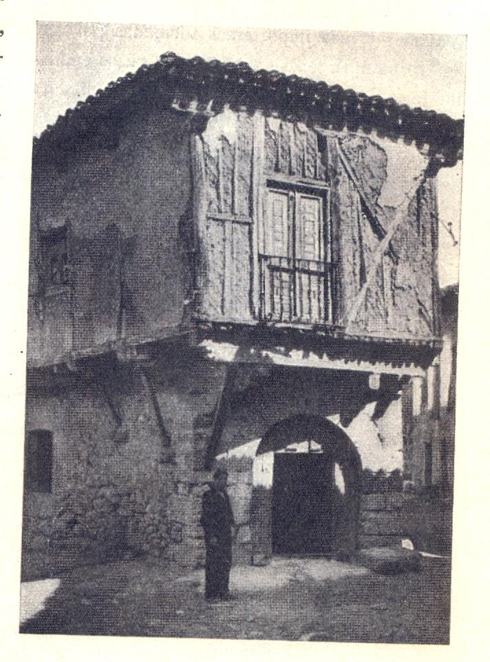 Casa con puerta y arco de medio punto, mampostería y balcón de repecho en el primer piso.