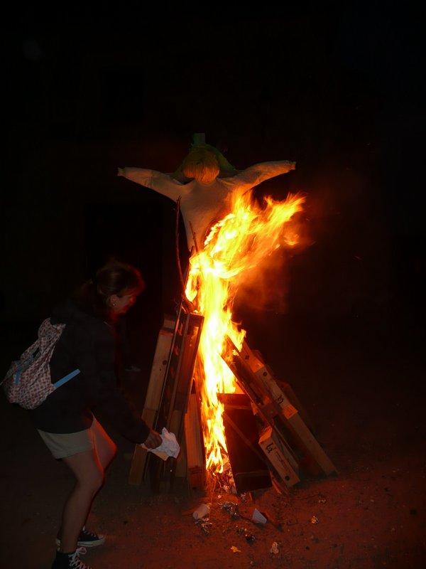Un pelele y otros enseres arden en la hoguera de San Juan. Una persona echa algo al fuego.