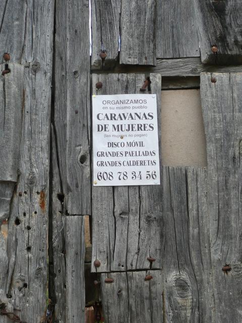 anuncio de una caravana de mujeres sobre una puerta desvencijada