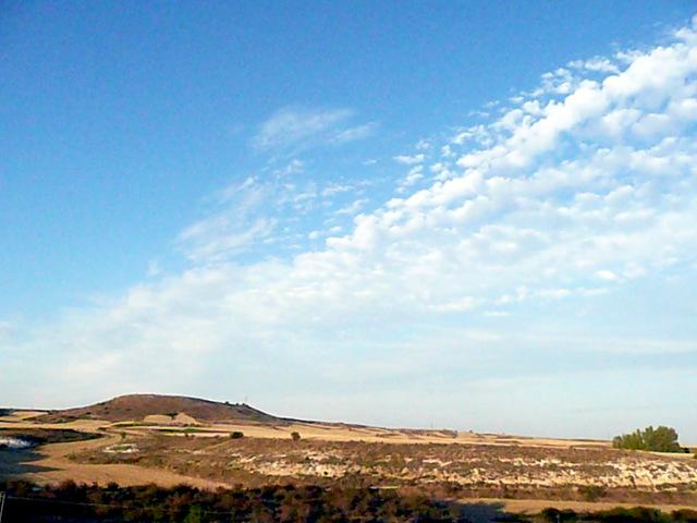 paisaje en tonos ocres coronado por nubes (cirros)