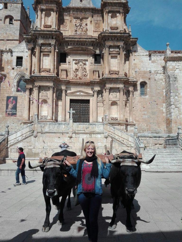 Joven posa en medio de los dos bueyes con la iglesia al fondo