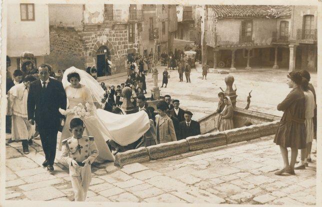 Comitiva nupcial precedida por niño de comunión subiendo las escaleras de la iglesia. Al fondo la plaza