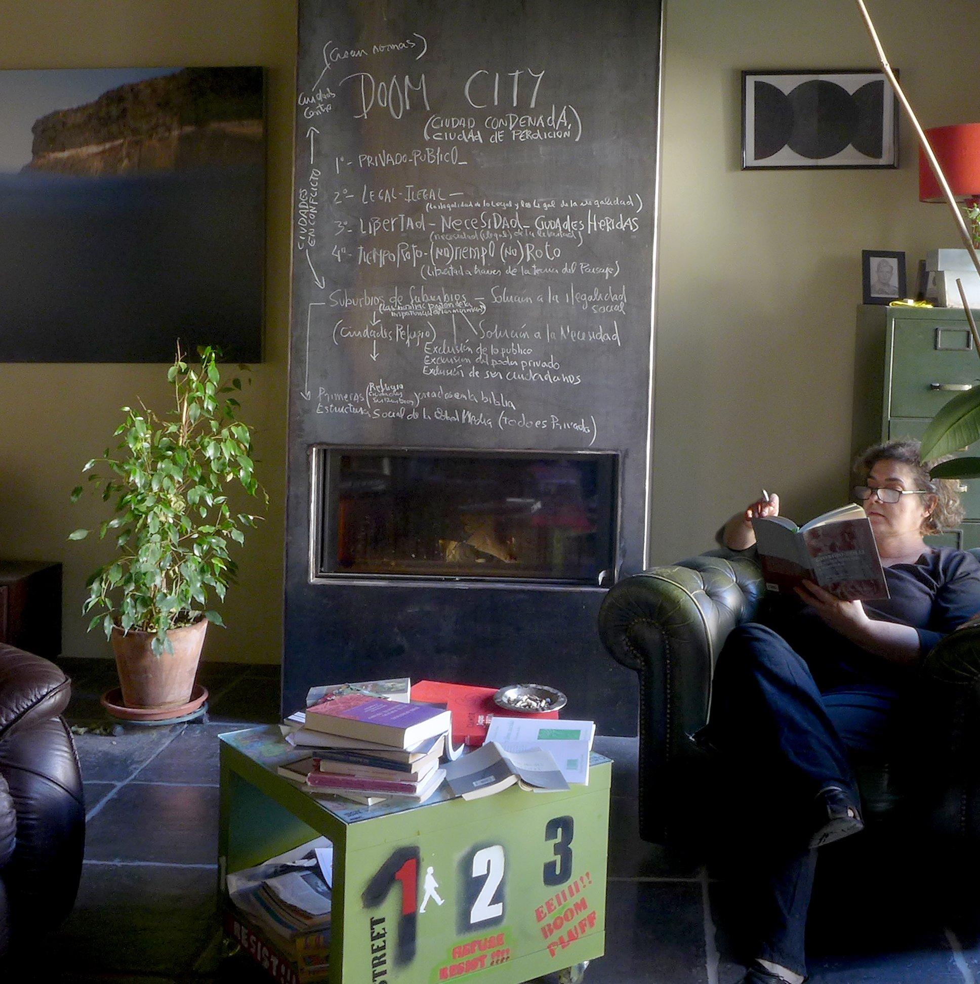 Montse sentada en un sillón en una esquina del salón de su casa. En el fondo una chimenea con una pizarra encima llena de anotaciones, como en un plan de trabajo. En primer plano una mesa cúbica con diversos objetosaAl fronte e o r -fot