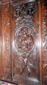 Un atlante sostiene un rosetón en el que se ve la virtud de la Templanza portando en la mano derecha una espada y en la izquierda un cálizaifiresPanel
