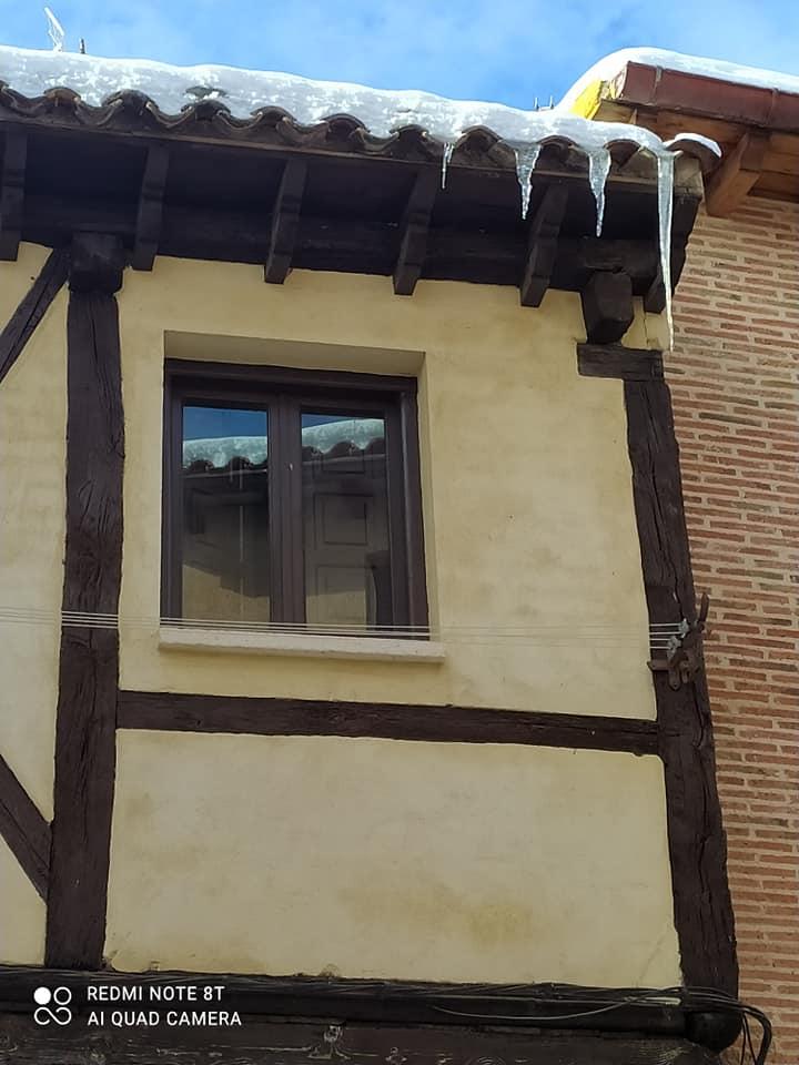 Una ventana en una fachada que refleja un tejado nevado. Del alero cuelgan churrulines.la