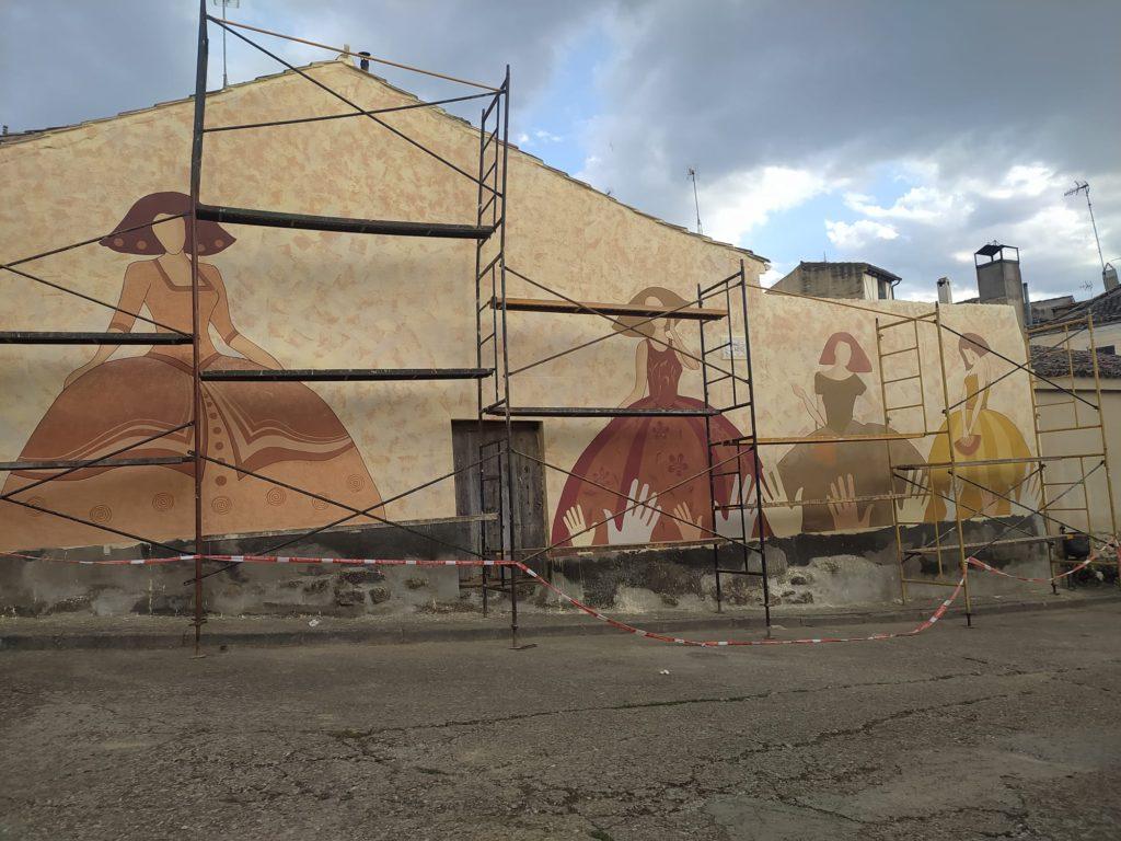 Detrás del andamio se ven las figuras femeninas y una serie de manos abajo del mural