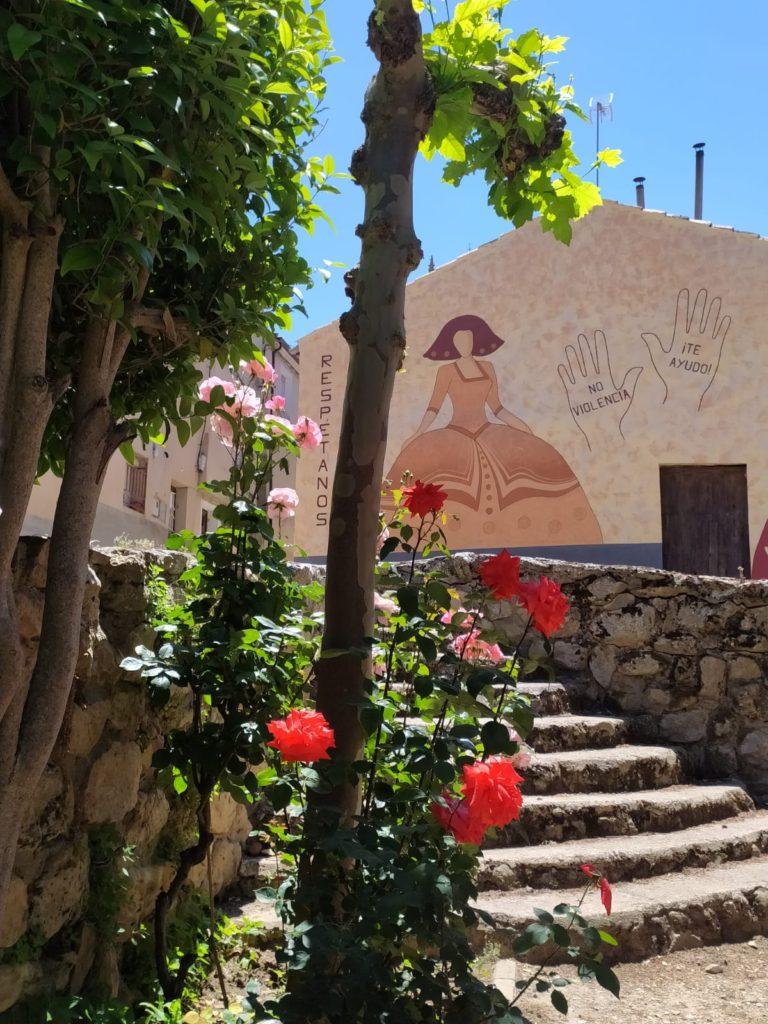 Rosal en primer término, escaleras y al fondo el mural con las leyendas