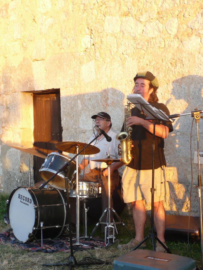 Primer plano de Lucas tocando el saxofón. En segundo plano el batería